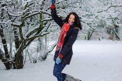 Active lächelnder junger Brunette im roten Schal, der Winterspiel draußen im schneebedeckten Park während eines Tages spielt Lizenzfreies Stockbild