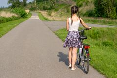 Active life. A woman with a bike enjoys the view at summer forest. stock photo