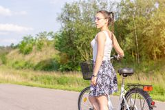 Active life. A woman with a bike enjoys the view at summer forest. royalty free stock image