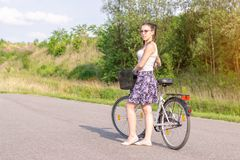 Active life. A woman with a bike enjoys the view at summer forest royalty free stock photos