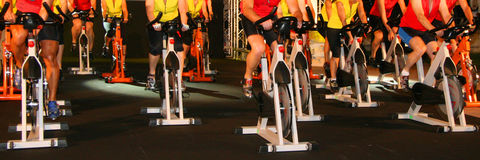 Active lifestyle. Men & women pedalling on stationery bikes Stock Photo