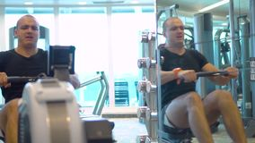 Young athlete makes an exercise on rowing simulator in gym reflecting in mirror stock footage