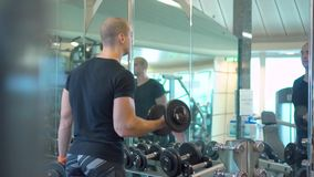 Young athletic man trains with dumbbells in gym reflecting in a mirror stock video footage