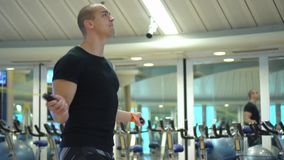 Young athletic man trains with a jumping rope in gym stock video