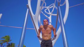 Young muscular guy doing exercise on uneven bars outdoor. Active lifestyle health self-development training stock footage