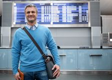 Delighted mature male is waiting for flight. Active lifestyle. Portrait of cheerful pleasant middle-aged man with bag is standing at international airport Royalty Free Stock Image