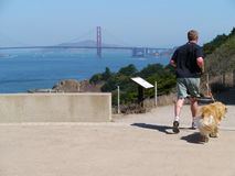 Active lifestyle in San Francisco. A runner and his Golden Retriever dog are out jogging on a beautiful sunny day in San Francisco Lincoln Park. The famous Royalty Free Stock Photos