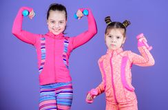 Active lifestyle. Sport and fitness for kids. Cute sisters doing gym fitness exercises with dumbbells. Little children. Developing physical fitness. Small girls royalty free stock photos