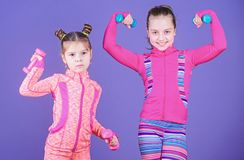 Active lifestyle. Sport and fitness for kids. Cute sisters doing gym fitness exercises with dumbbells. Little children. Developing physical fitness. Small girls royalty free stock photography