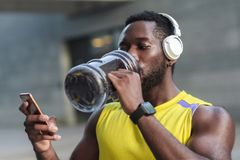 Active lifestyle. Strong african man drinking water after hard w. Orkout. Posting in instagram, looking at monitor new smartphone royalty free stock photo