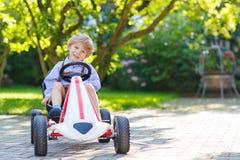 Active little boy driving pedal car in summer garden Royalty Free Stock Photos