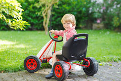 Active little boy driving pedal car in summer garden Stock Images