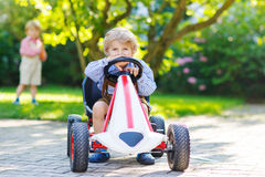 Active little boy driving pedal car in summer garden Stock Image