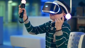 Active little boy enjoying virtual reality with motion controllers in his hands. Professional shot in 4K resolution. 093. You can use it e.g. in your Royalty Free Stock Photo