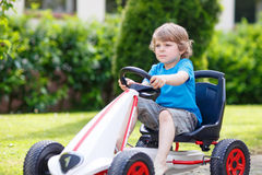 Active little boy having fun and driving toy race car Stock Photo