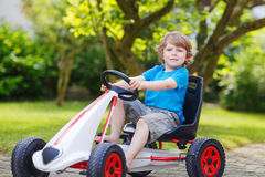 Active little boy having fun and driving toy race car Royalty Free Stock Photos
