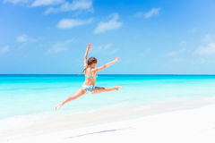 Active little girl at beach having a lot of fun on the shore making a leap Royalty Free Stock Photos