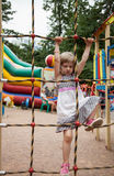 Active little girl climbing on a ladder Stock Images