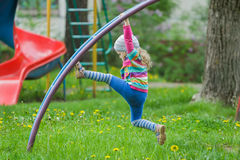 Active little girl climbing monkey bar outdoors on spring playground. Active little girl is climbing monkey bar outdoors on spring playground Royalty Free Stock Image