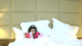 Active little girl dancing in bed stock footage