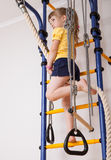 Active little girl doing sport exercises. On a ladder at home stock photos