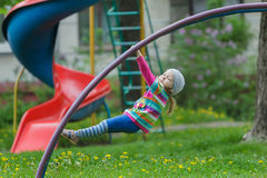 Active little girl hanging on jungle gym outdoors on spring playground. Active little girl is hanging on jungle gym outdoors on spring playground Royalty Free Stock Images