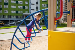 Active little girl on the playground. Active little girl playing on the playground Royalty Free Stock Image