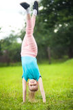 Active little girl turning outdoors, sport and children. Cute athletic schooler girl  tumbling, turning, turn handsprings in the park, having fun. Sunny summer Royalty Free Stock Photo