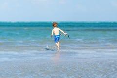 Active little kid boy having fun on Miami beach, Key Biscayne. Happy cute child running near ocean on warm sunny day royalty free stock photography