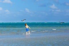 Active little kid boy having fun on Miami beach, Key Biscayne. Happy cute child running near ocean on warm sunny day stock photography
