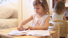 Active little preschool age child, cute toddler girl with blonde curly hair, drawing picture on paper using colorful. Pencils and felt-tip pens, sitting at stock footage
