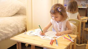 Active little preschool age child, cute toddler girl with blonde curly hair, drawing picture on paper using colorful. Pencils and felt-tip pens, sitting at stock video
