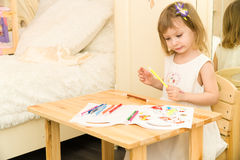 Active little preschool age child, cute toddler girl with blonde curly hair, drawing picture on paper using colorful. Pencils and felt-tip pens, sitting at royalty free stock image