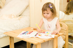 Active little preschool age child, cute toddler girl with blonde curly hair, drawing picture on paper using colorful. Pencils and felt-tip pens, sitting at royalty free stock photo