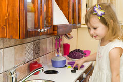 Active little preschool age child, cute toddler girl with blonde curly hair, shows playing kitchen, made of wood, plays royalty free stock photography