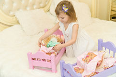 An active little preschool child, a pretty little girl with a blond curly hair, plays with her dolls, puts them to sleep Royalty Free Stock Photography
