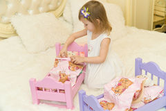 An active little preschool child, a pretty little girl with a blond curly hair, plays with her dolls, puts them to sleep Royalty Free Stock Photo