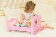An active little preschool child, a pretty little girl with a blond curly hair, plays with her dolls, puts them to sleep Stock Images