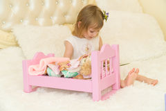 An active little preschool child, a pretty little girl with a blond curly hair, plays with her dolls, puts them to sleep Royalty Free Stock Image