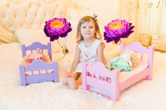 An active little preschool child, a pretty little girl with a blond curly hair, plays with her dolls, puts them to sleep Stock Photos