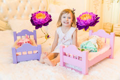 An active little preschool child, a pretty little girl with a blond curly hair, plays with her dolls, puts them to sleep Stock Photo