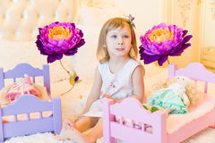 An active little preschool child, a pretty little girl with a blond curly hair, plays with her dolls, puts them to sleep Royalty Free Stock Images
