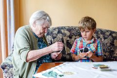 Active little preschool kid boy and grand grandmother playing card game together at home. Little child and retired women having fun. Happy family: grandchild Royalty Free Stock Image