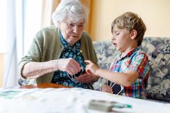 Active little preschool kid boy and grand grandmother playing card game together at home stock photo