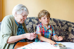 Active little preschool kid boy and grand grandmother playing card game together at home Royalty Free Stock Photography