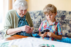 Active little preschool kid boy and grand grandmother playing card game together at home Royalty Free Stock Image