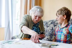 Active little preschool kid boy and grand grandmother playing card game together at home. Little child and retired women having fun. Happy family: grandchild Stock Photos