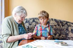 Active little preschool kid boy and grand grandmother playing card game together at home. Little child and retired women having fun. Happy family: grandchild Stock Image