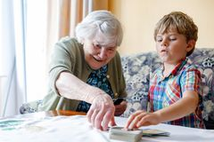 Active little preschool kid boy and grand grandmother playing card game together at home. Little child and retired women having fun. Happy family: grandchild Royalty Free Stock Photos