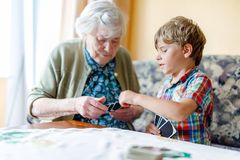Active little preschool kid boy and grand grandmother playing card game together at home. Little child and retired women having fun. Happy family: grandchild Stock Images